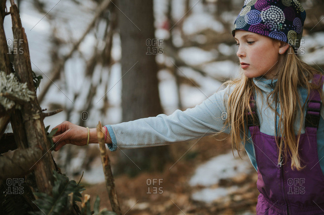 Young girl building a teepee in the woods