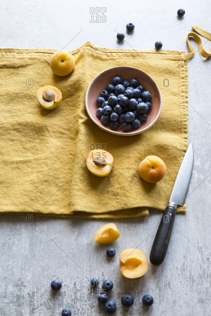 Overhead view of sliced apricots and blueberries in a bowl