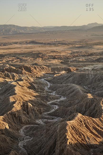 Scenic view of river between barren mountain ranges