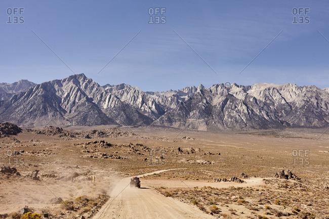 Car on dirt road through vast desert valley