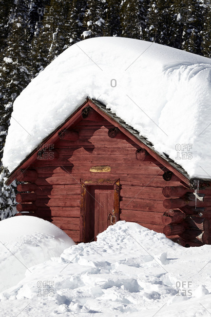 Snow-covered log cabin in the forest
