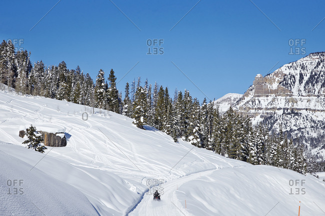 Snowmobile on snow-covered road through mountains