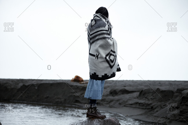 Person wrapped in Native American blanket standing on a rock overlooking a river