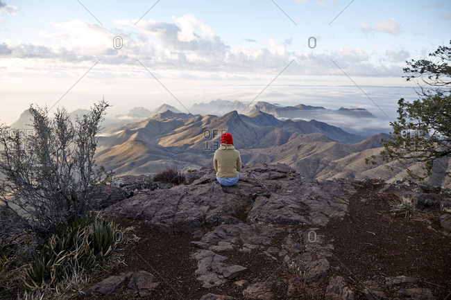 Person sitting on rocky outcrop overlooking vast mountain range