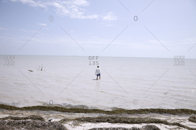 Person wading in shallow water of lake