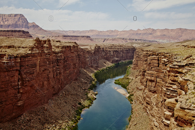 Scenic view of river with still, blue water through narrow canyon of red rocks
