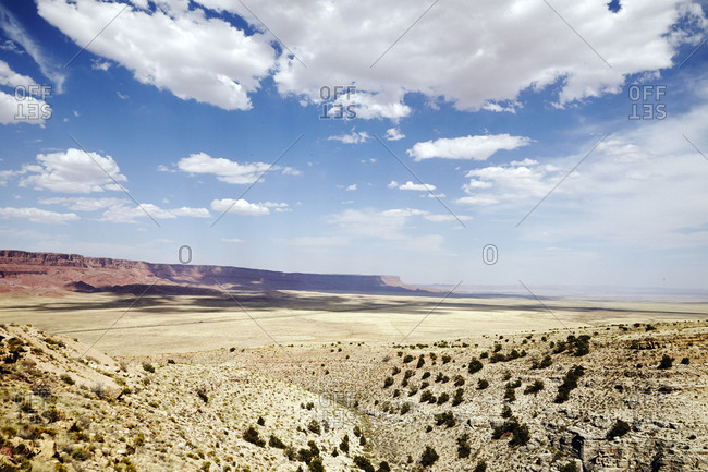 Vast desert plateau with sparse vegetation and blue sky with clouds