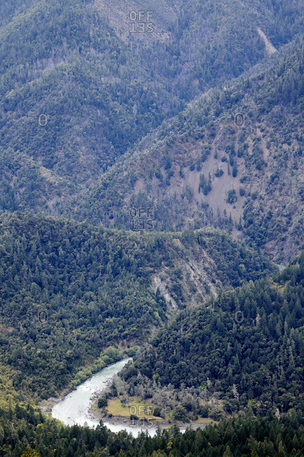Scenic river in forested wilderness area with steep mountain slopes