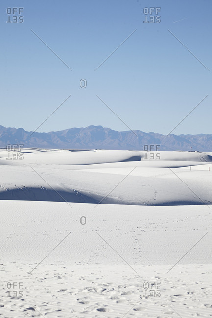 Desert sand dunes with mountains in the distance