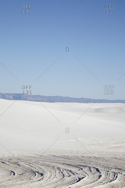 Vast sand dunes in the desert with mountains in the distance