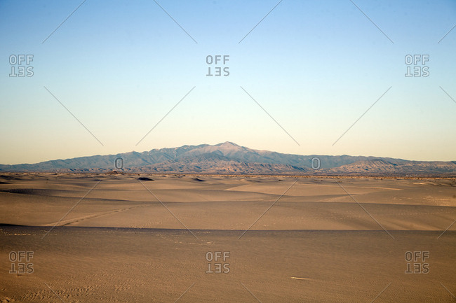 Barren desert landscape with mountain range in the distance