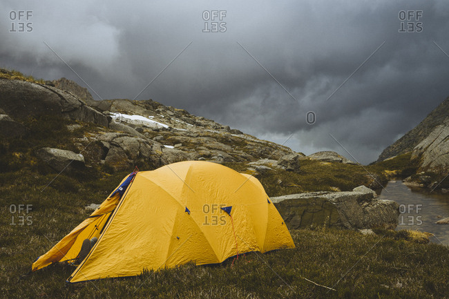 Tent sitting in front of dramatic sky backdrop.