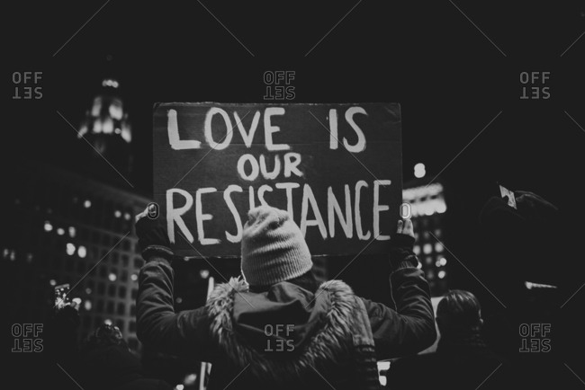 """Protester holding sign reading """"Love is our Resistance"""""""