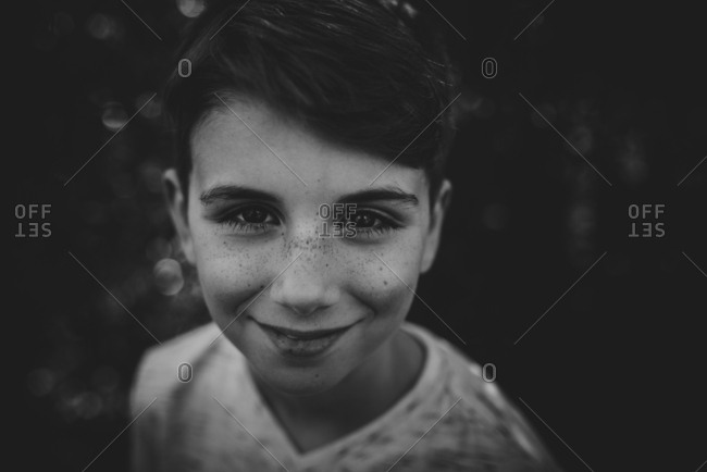 Portrait of a smiling boy with freckles in black and white