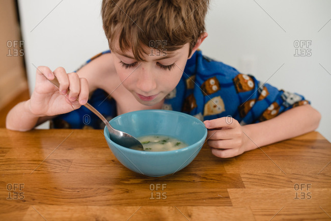 Young boy eating soup
