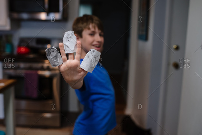 Boy wearing hand drawn puppets on his fingers