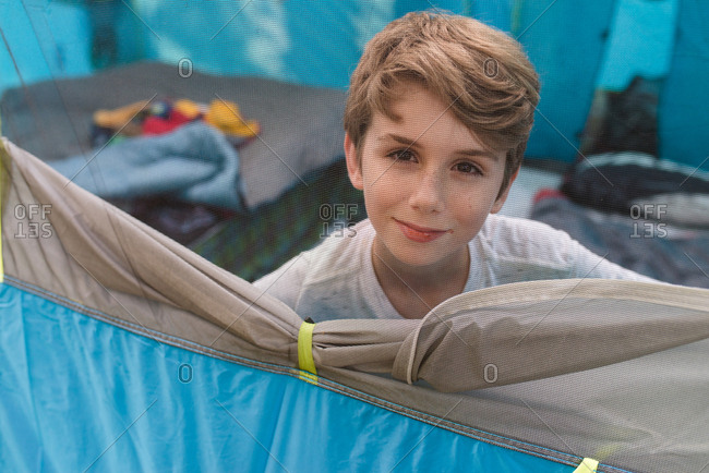 Boy looking out tent screen while camping