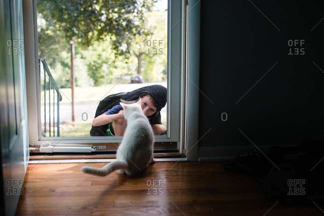 Boy playing with white cat through glass door