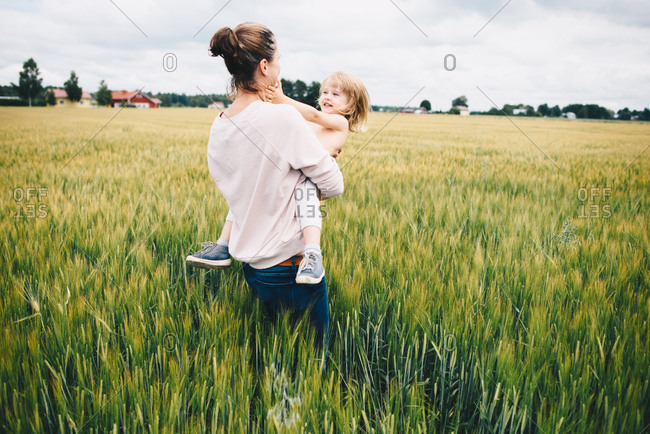 Woman dancing with toddler in a field