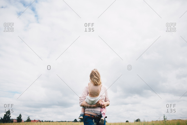 Woman holding toddler in a field