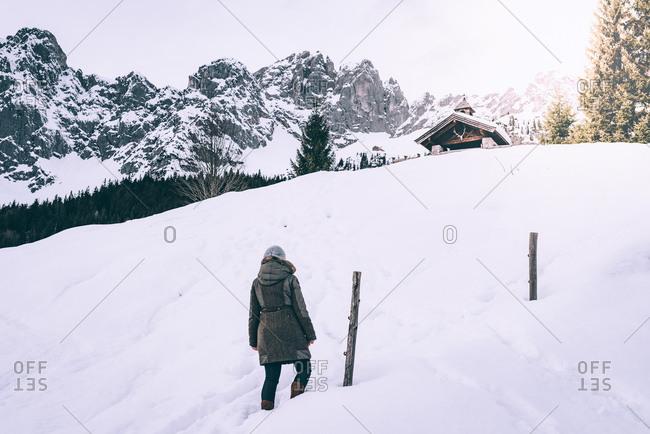Rear view of woman walking in snow in rural Austria