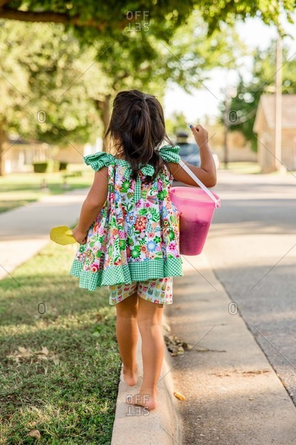 Little girl walking on curb carrying bucket and shovel