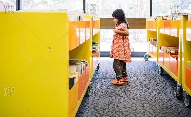 Girl looking for books in a library