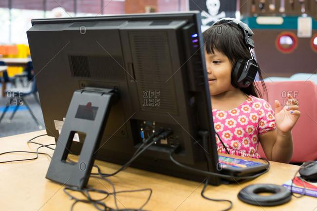 Little girl wearing headphones using computer
