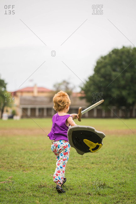 Girl running with toy swords and shields