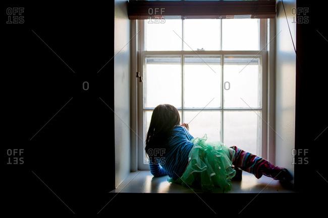 Little girl wearing tutu sitting on windowsill looking outside