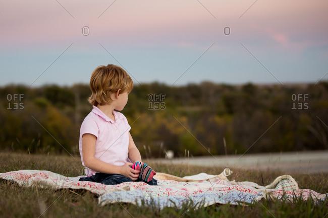 Little girl sitting on blanket watching sunset