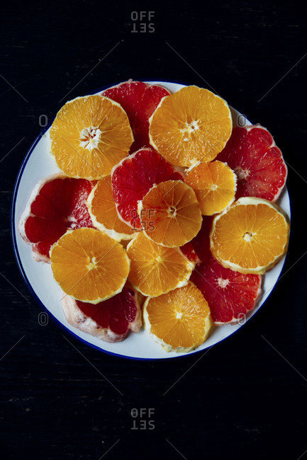 Orange and grapefruit citrus slices stacked on a plate