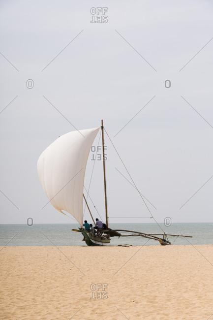 A traditional wooden catamaran on the beach in Negombo, Sri Lanka