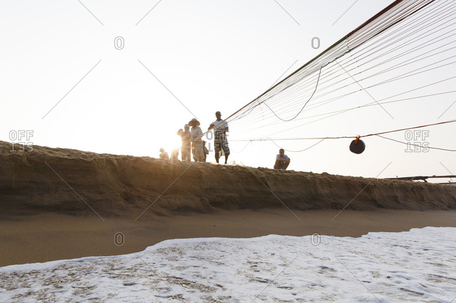 Sri Lanka - January 9, 2018: Local fishermen on a beach in Sri Lanka pull in long fishing nets from the shore early in the morning
