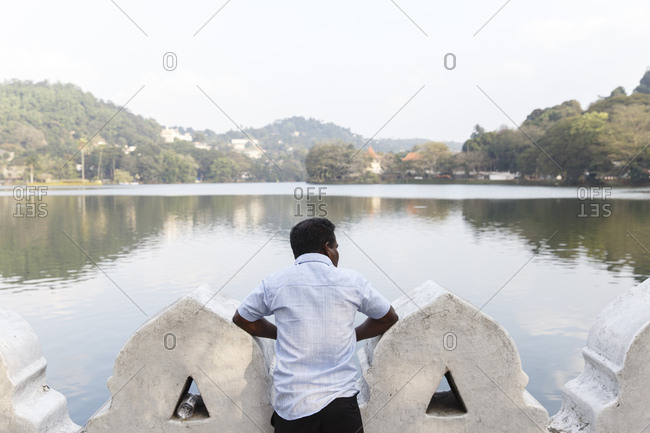 A man looks out over the Bogambara Lake in the middle of the city of Kandy, Sri Lanka