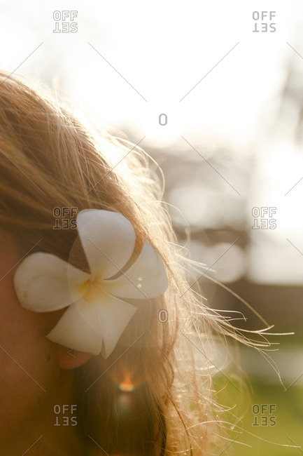 A woman wearing a white tropical flower behind her ear