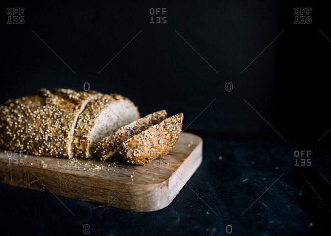 Still life of partly sliced multi seed loaf of bread