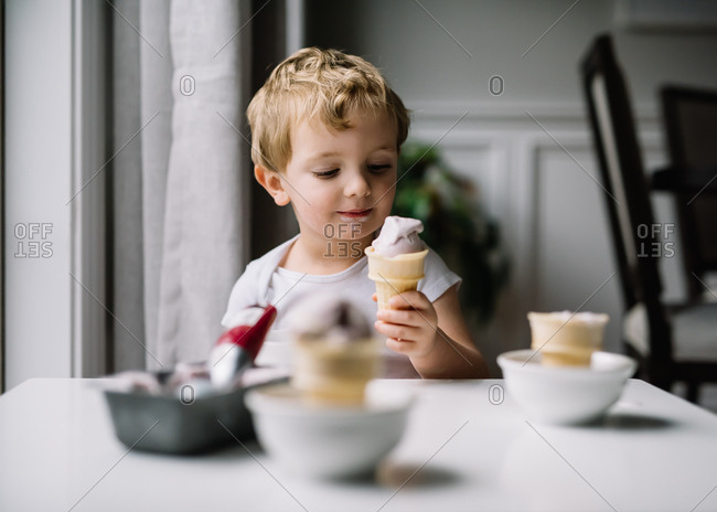 Young boy looking lovingly at ice cream cone he is eating