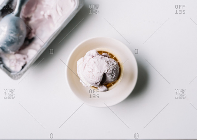 Overhead view of ice cream cone standing in a bowl and scoop in tub of homemade ice cream