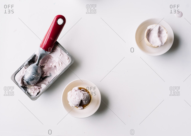 Overhead view of scoop in tub of homemade ice cream and ice cream cones in bowls