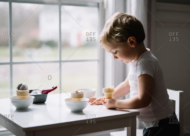 Young boy thoughtfully looking into ice cream cone