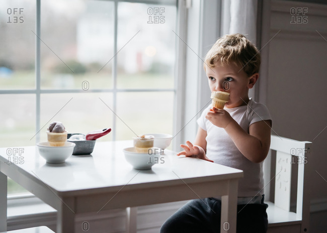 Young boy absorbed in the moment while eating ice cream cone