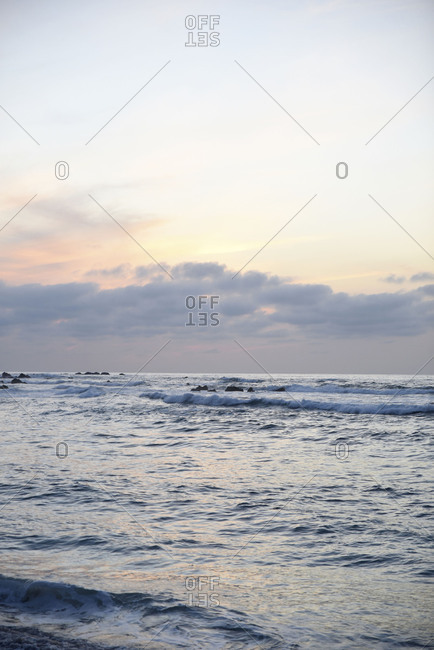 Scenic oceanfront sunset with wavy tide