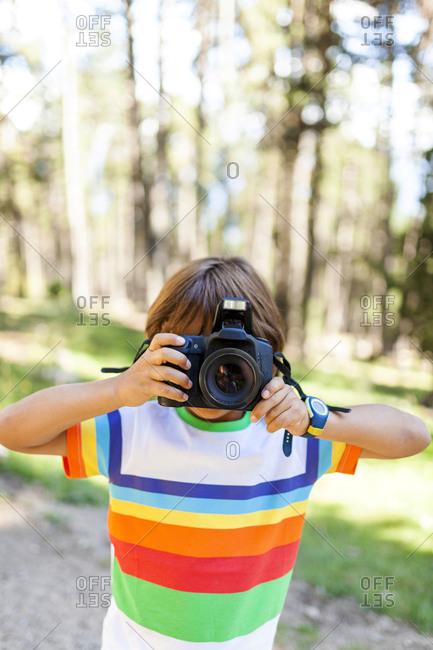 Boy looking through DSLR at camera