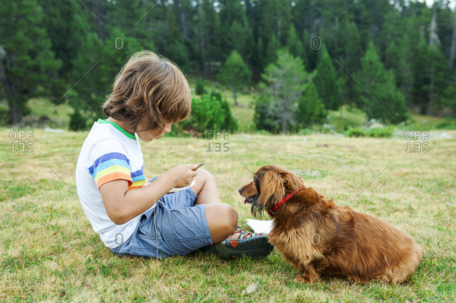 Young boy sharing lunch with his friendly dog