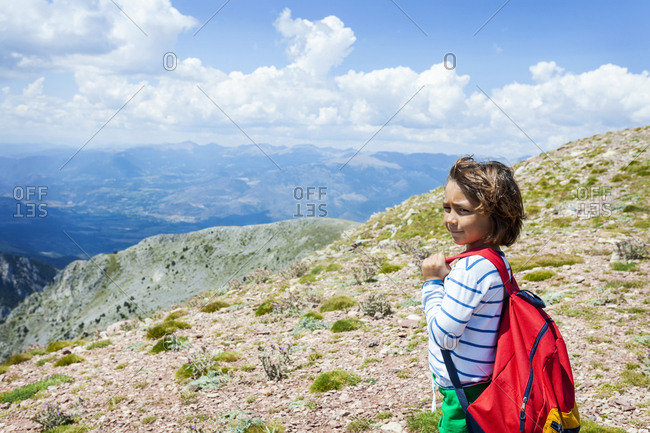 Boy enjoying impressive mountain view  on backpacking vacation