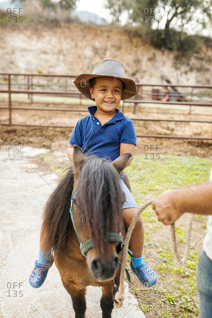 Little boy in leather hat riding pony
