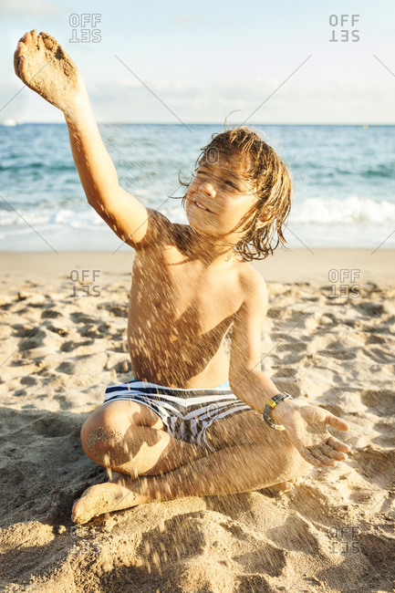 Energetic boy playing with wind and sand on vacation at the beach