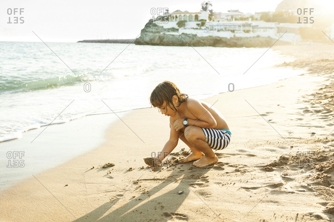 Boy crouching down to draw in sand at sundown