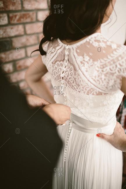 Mother-of-bride helping daughter fasten wedding gown